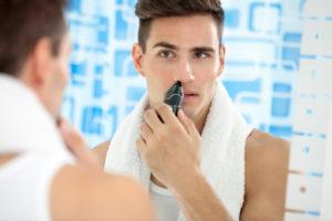 Mann rasiert die Nasenhaare