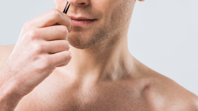 Mann zupft Nasenhaare